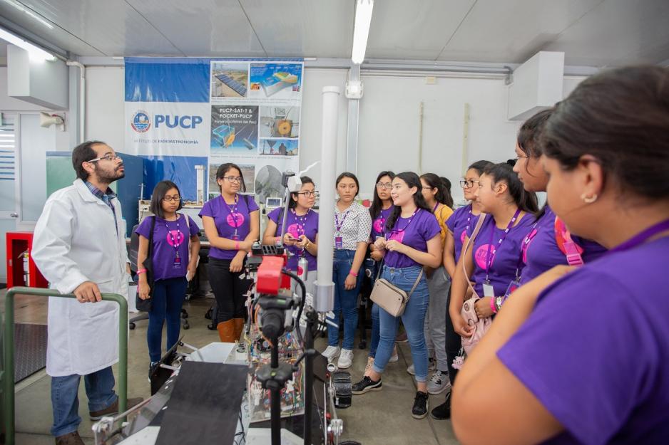 Un grupo de 10 alumnas están en un laboratorio PUCP escuchando la explicación del expositor.