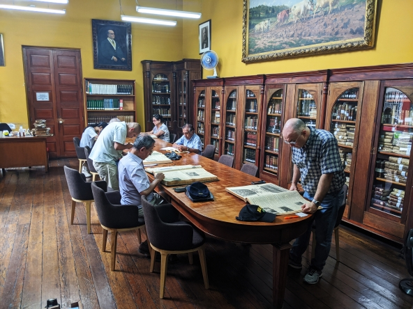 Tradicional sala de lectura de la biblioteca del IRA. Es una toma panorámica. En una mesa larga de madera hay 7 investigadores. El piso es de madera. Detrás, estantes de madera con libros hasta una altura aproximada de metro ochenta. Encima de ellos, las pareces, de techos altos, tienen cuadros.